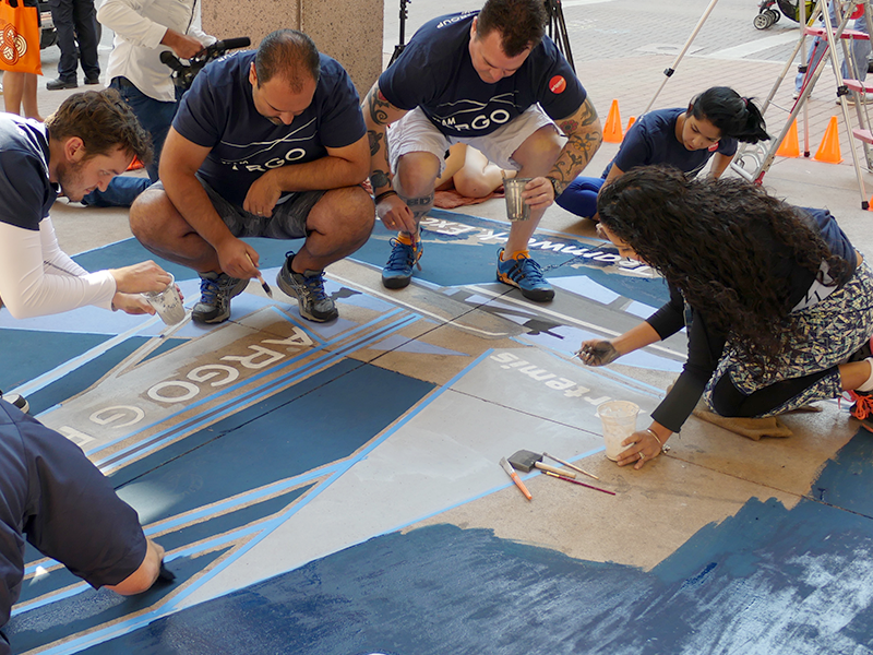Argo employees working together to paint an intricate design on a sidewalk