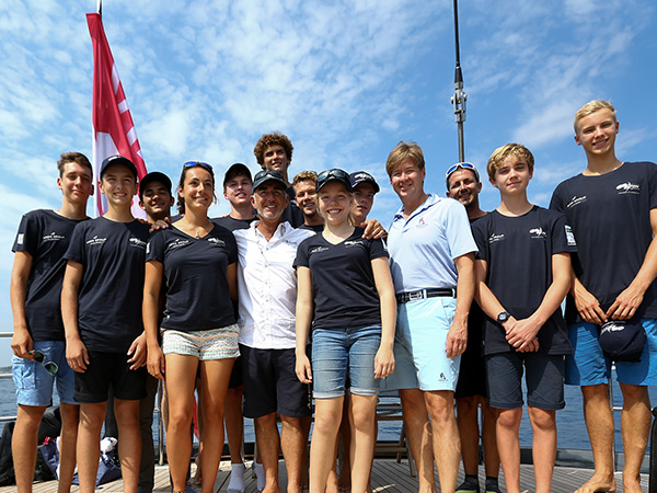 CEO Mark Watson and young sailors standing on a sailboat