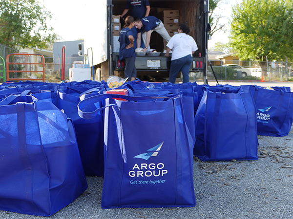 A bag filled with food and Argo employees unloading a truck in the background