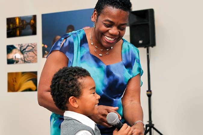 Woman in colorful dress smiling and holding microphone for young boy