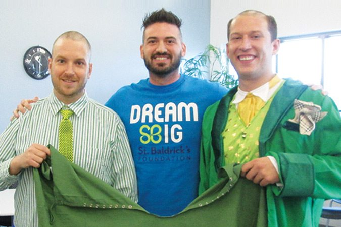 Men wearing green who shaved their heads to help raise funds for St. Baldrick's Foundation
