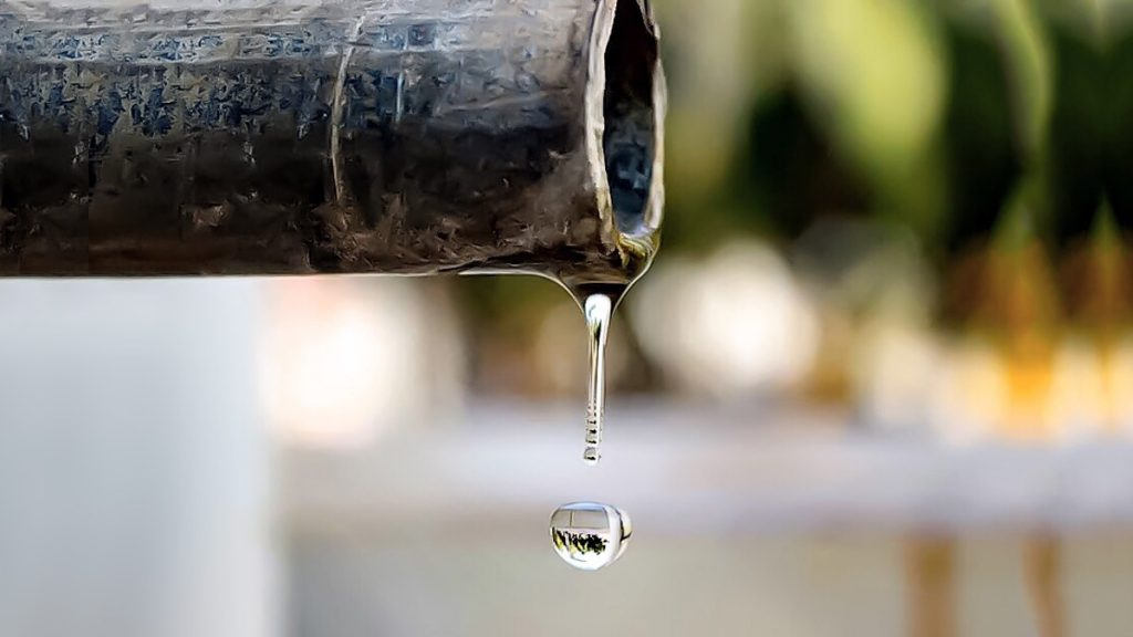 Water droplet falling from a lead pipe with blurred background