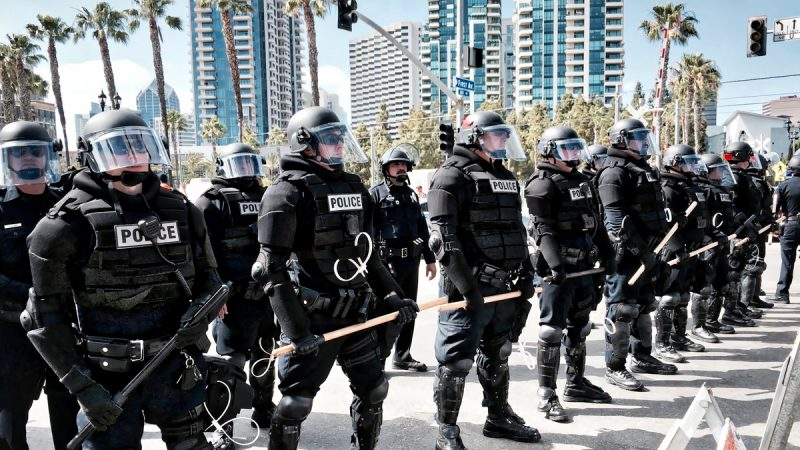 Line of policeman in riot gear stand holding batons