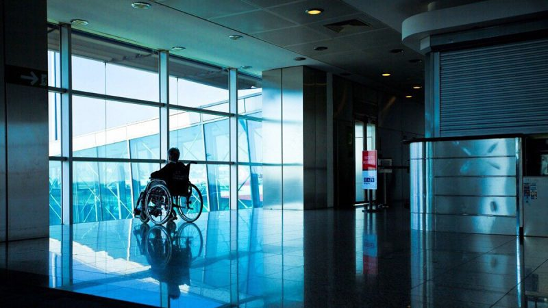 Silhouette of individual in a wheelchair sitting in front of large picture window