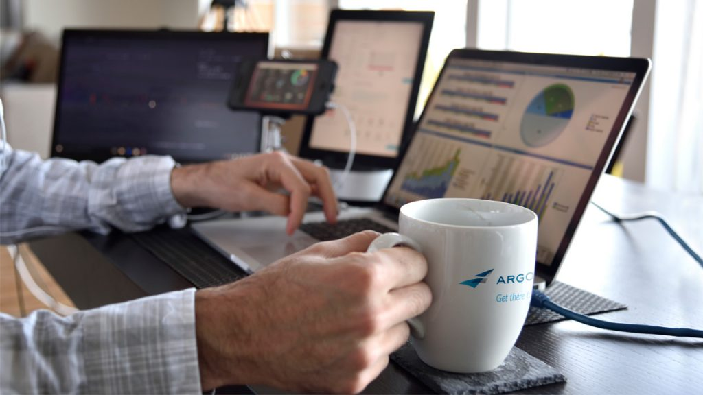 Male hands working on laptop while holding Argo Group branded coffee mug
