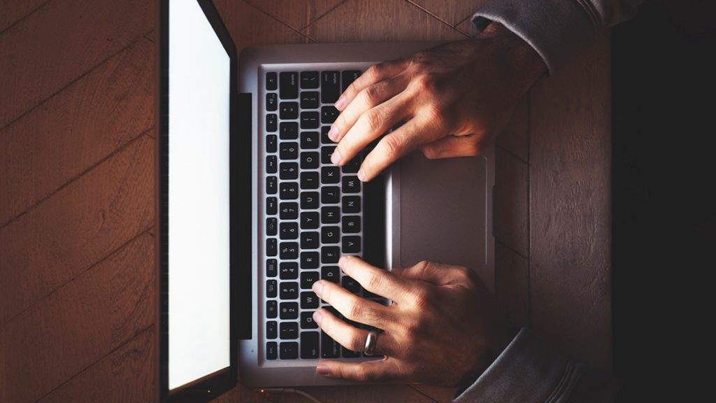 Male hands typing on a laptop, aerial view