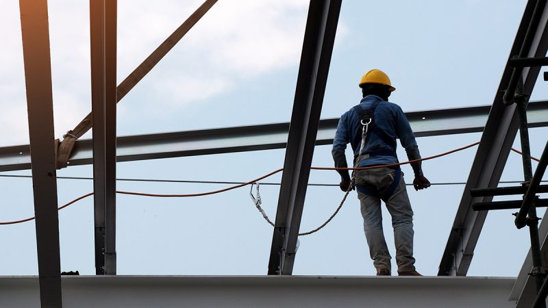 Man in hard hat standing on steel I beam and connected to safety harness
