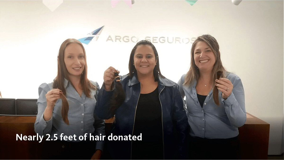 Argo Seguros female employees hold donated locks of their hair