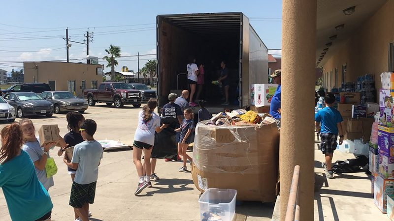 Volunteers loading boxes into the back of a large container truck