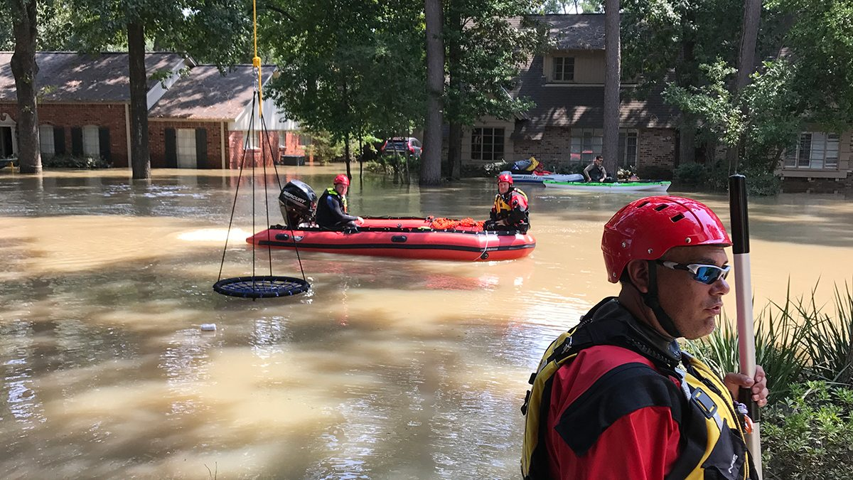 Rescue workers in an inflatable raft navigate down a flooded street