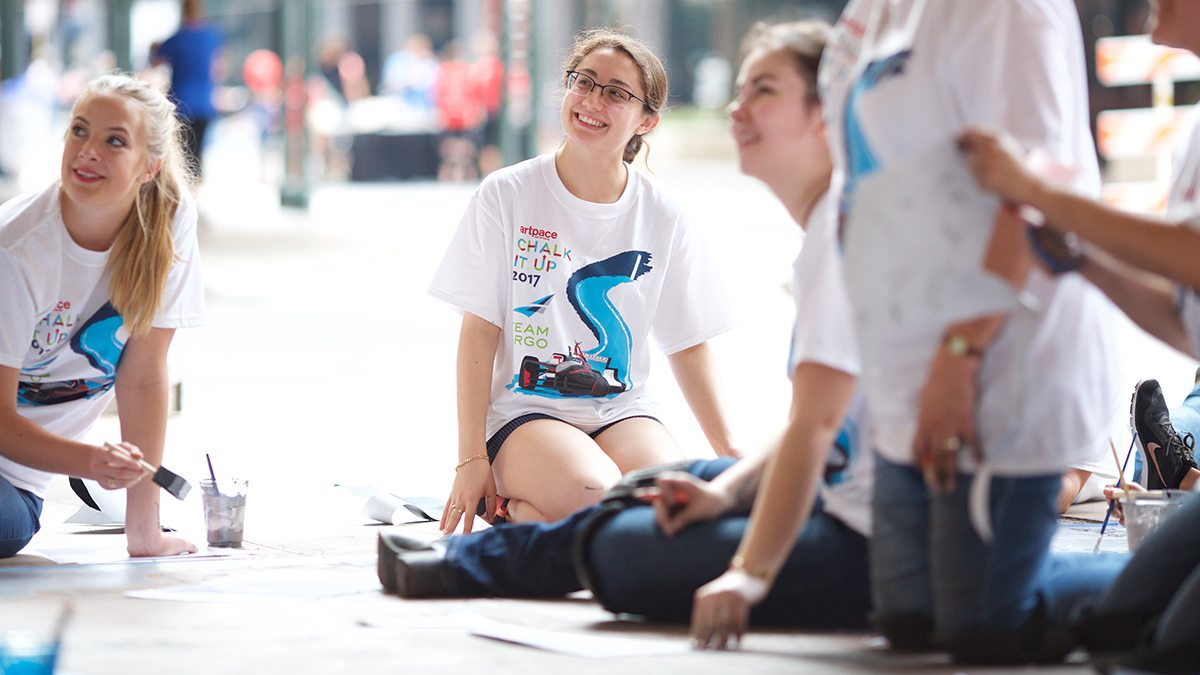 Young girl in glasses smiling as she works on sidewalk chalk art during 2017 Chalk It Up event
