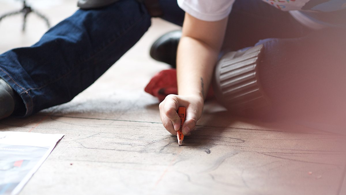 Small child's hand holding a chalk writing utensil, drawing on the pavement