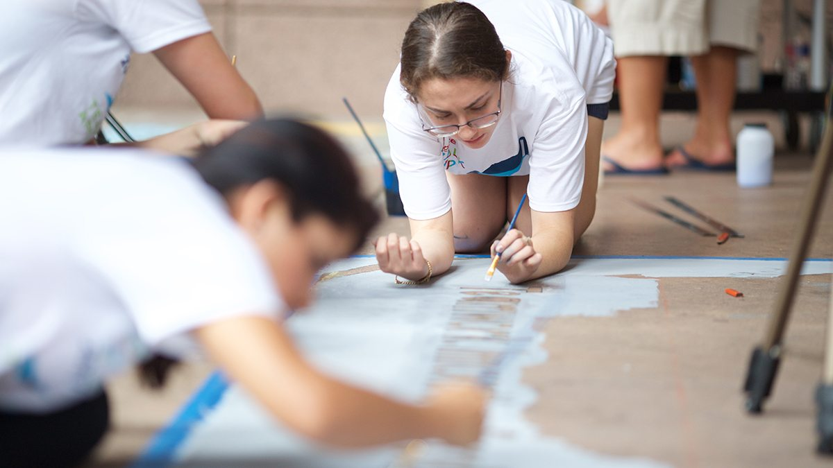 Young girl in glasses painting in letters during San Antonio's Chalk It Up event