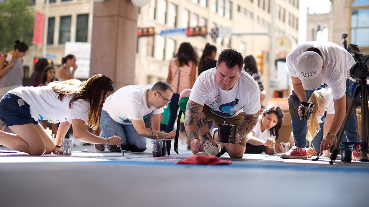 People painting sidewalk chalk art in front of Argo Group building in San Antonio