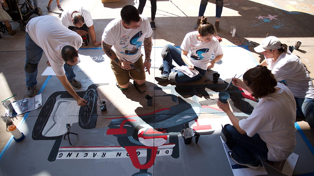 People painting race car with sidewalk chalk during San Antonio's Chalk It Up