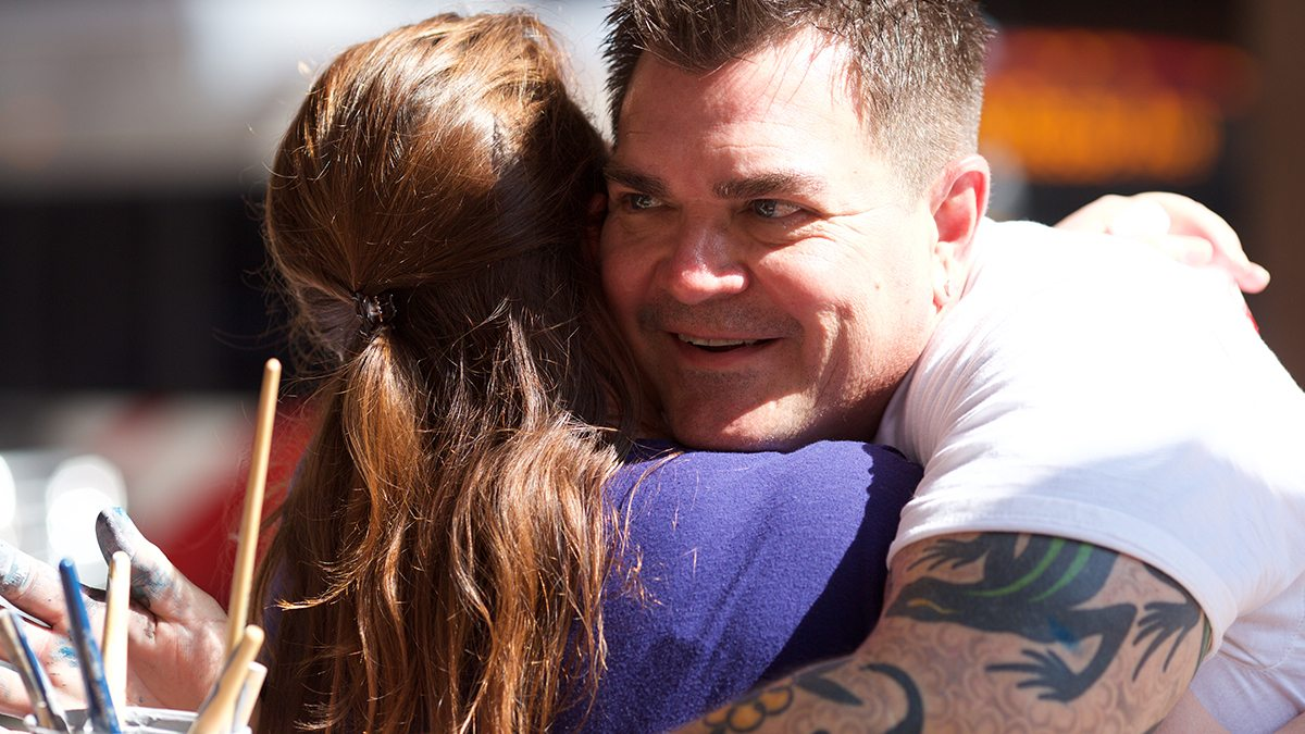 Man with tattooed arms hugging a young woman at San Antonio's Chalk It Up