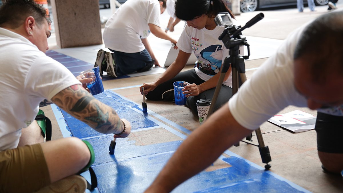 Individuals filling in blue paint during San Antonio's Chalk It Up event
