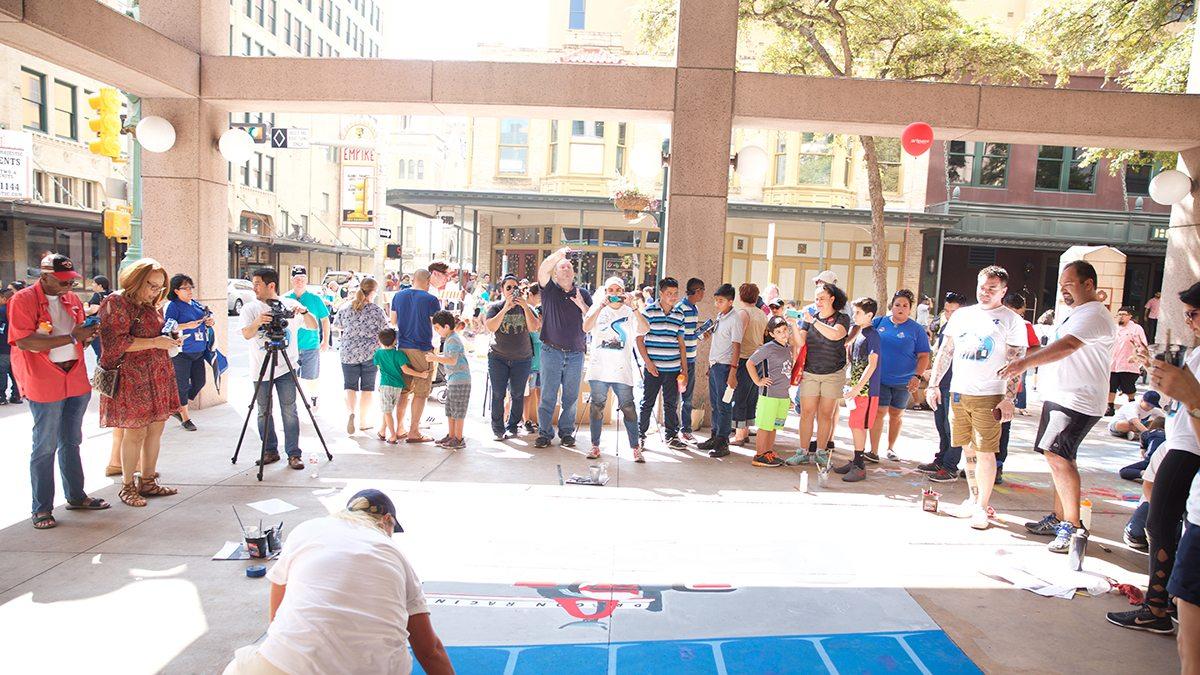 Onlookers examine sidewalk chalk art in front of Argo Group building during Chalk It Up in San Antonio