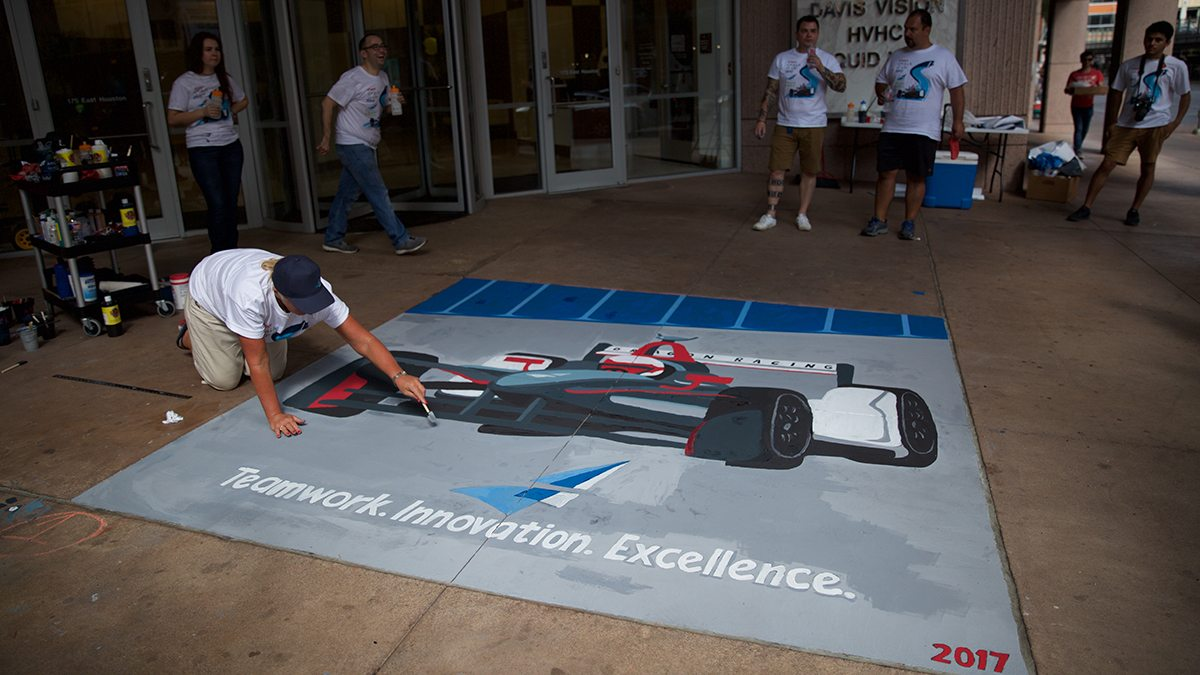 Man puts finishing touches on sidewalk chalk art in front of Argo Group building in San Antonio