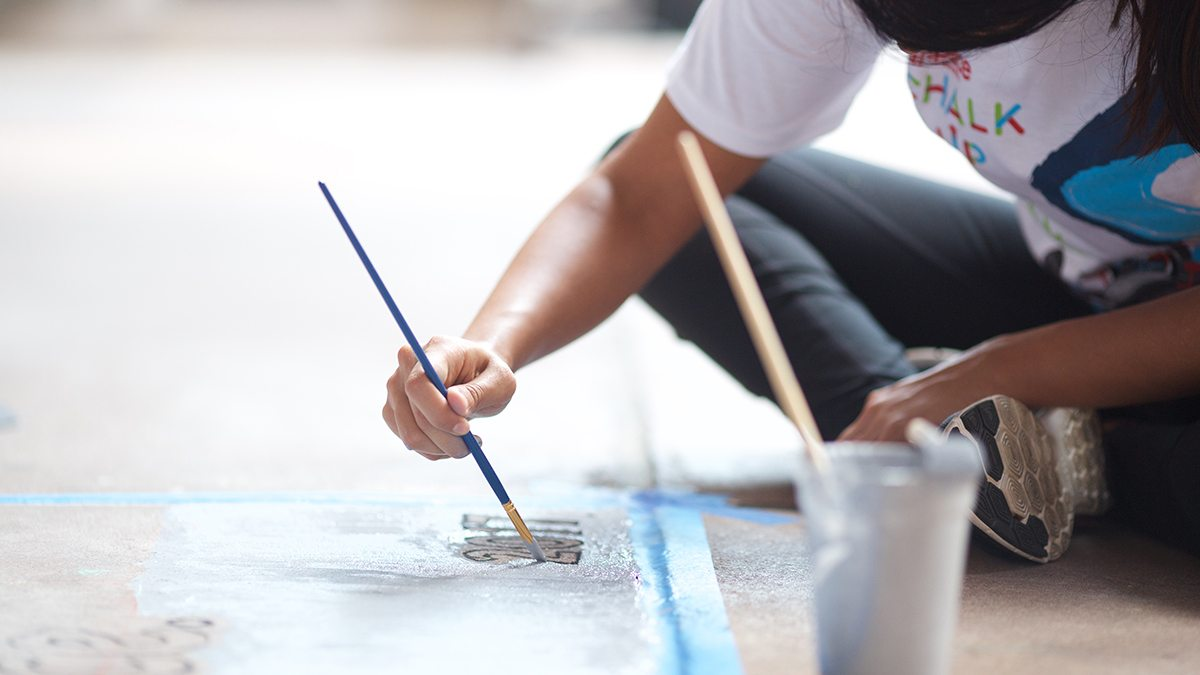 Young girl using paintbrush to write 2017 on chalk art during San Antonio's Chalk It Up