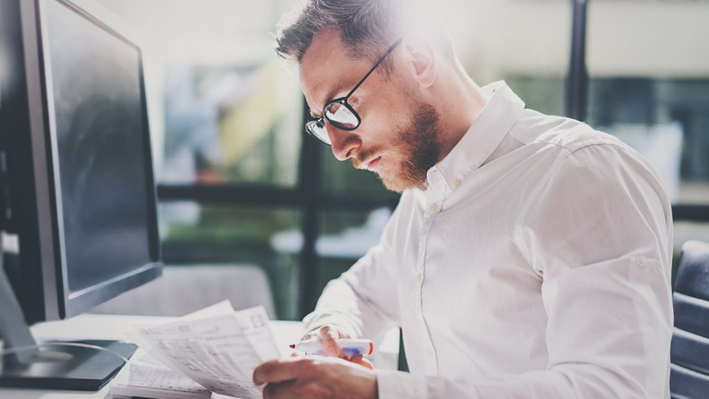 Young man with beard and glasses staring at documents in front of a computer monitor