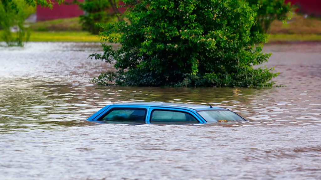 Car in high floodwaters that are almost up to its roof