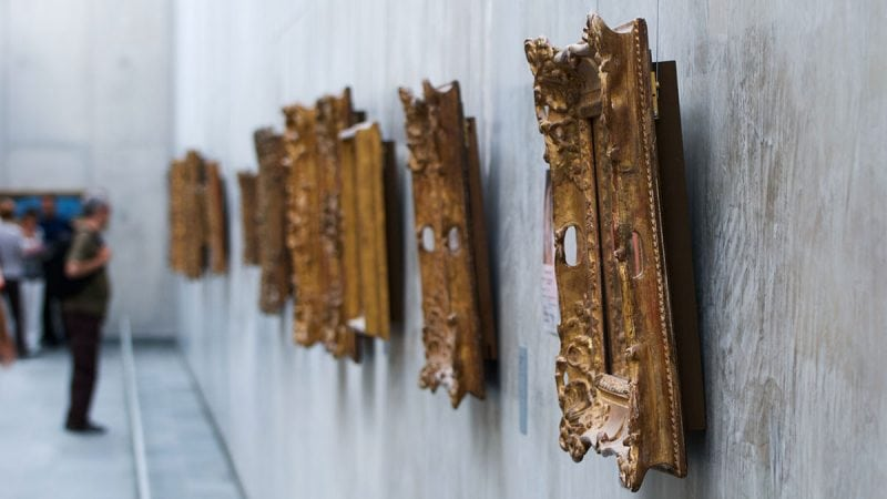 Ornate gold frames hanging on a gallery wall