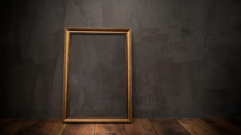 Empty gold frame leaning against a dark wall
