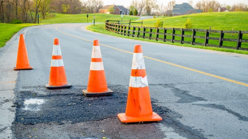 Orange road cones surrounding a patched pothole on a small rural road