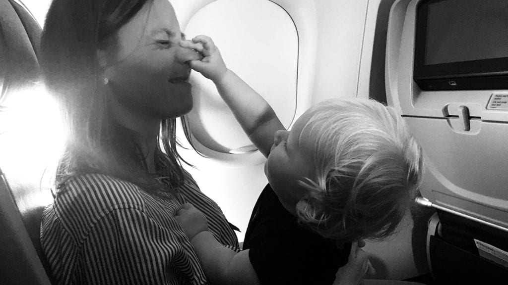 Women at Argo Katie Partington getting her nose pinched by a toddler on a plane