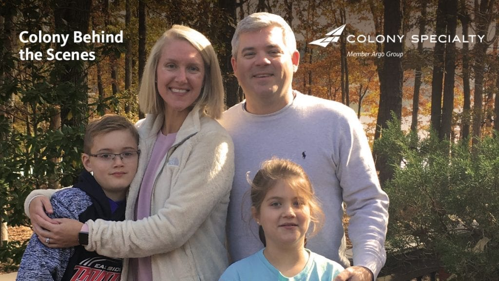 Colony Specialty employee Kelly Killimett posing with her family in wooded area