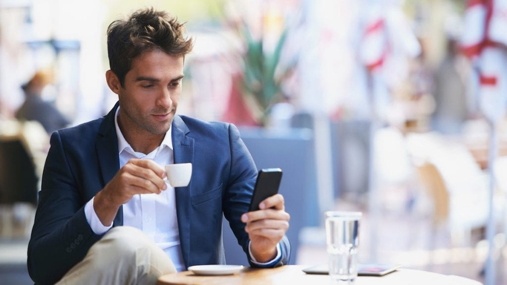 Young businessman reading a text while sitting at an outdoor cafe