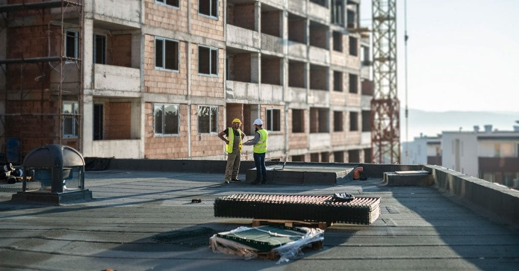 Two men in hard hats standing on the roof of a building under construction.