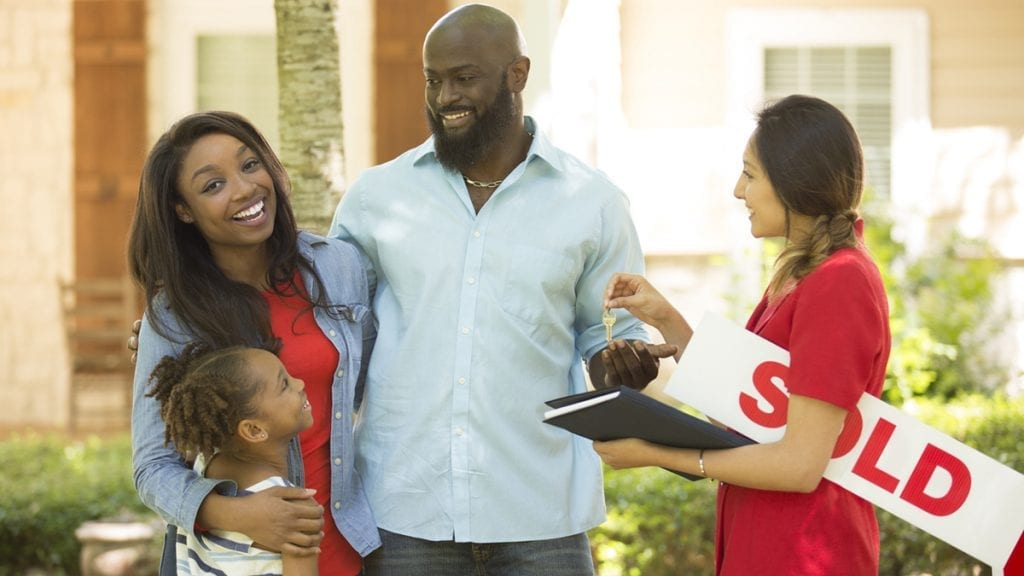 Happy young family accepting the keys to their new home