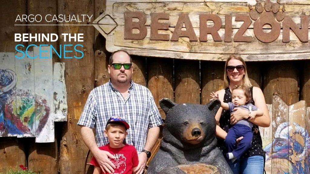 Argo Casualty employee Adam Verhoeks posing with family next to bear sculpture