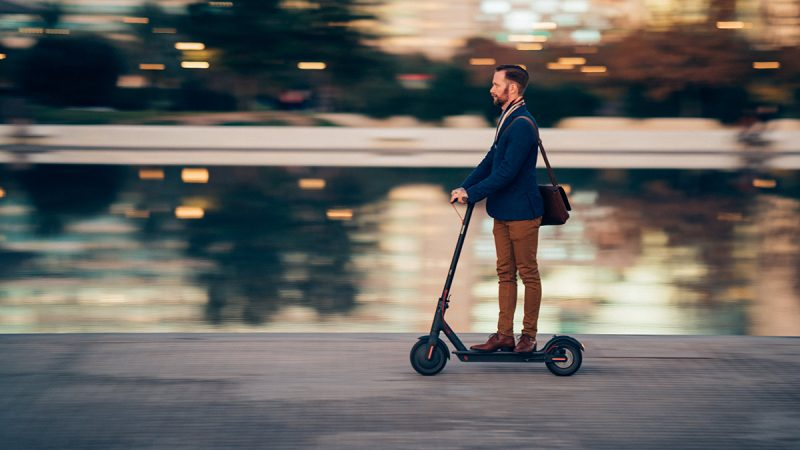 Sharply dressed man traveling on rented scooter in urban environment