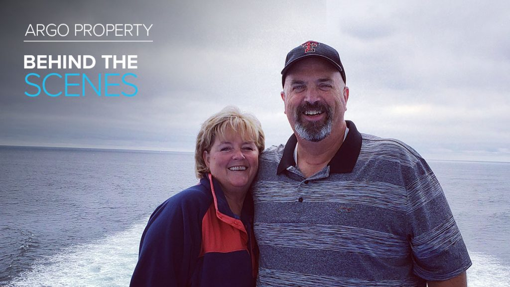 Argo Property employee Mindy Riza poses with man in front of ocean