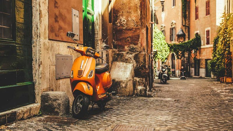 Vespa scooters parked in quaint Italian alleyway