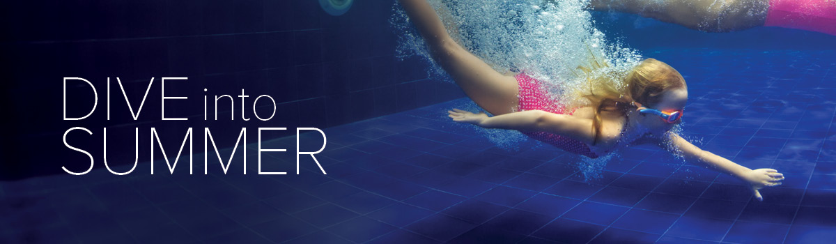 Young girl in swim goggles diving down toward the bottom of a pool