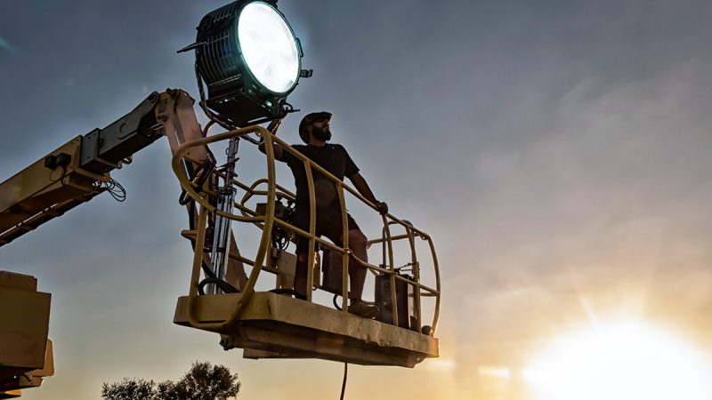 Man standing in a cherrypicker operating a large spotlight