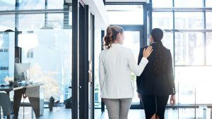 Two young professional women walking out of an office