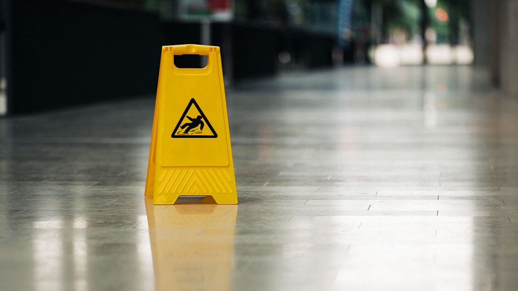 Yellow caution sign in the middle of a slippery looking floor
