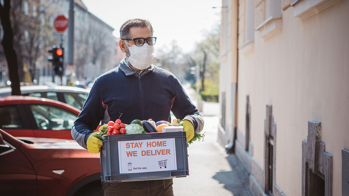 Man wearing a mask and delivering food items