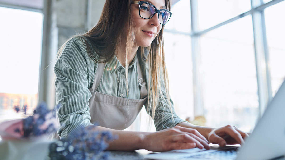Female small business owner in apron typing on a laptop