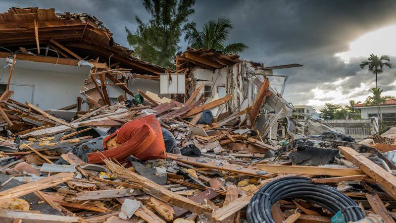 Debris strewn in front of damaged house following a natural disaster