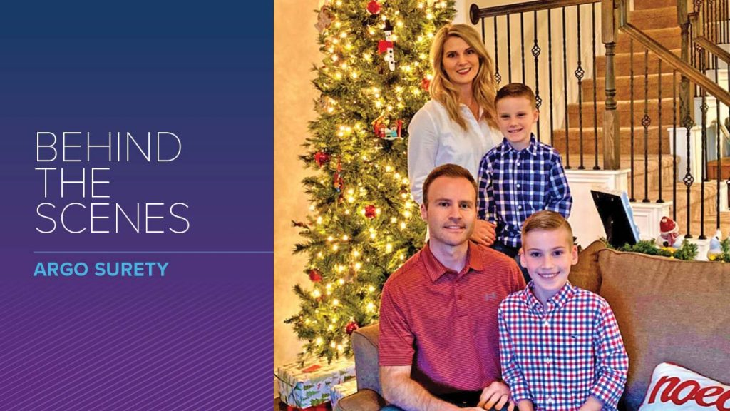 Argo Surety employee Kyle Davis poses with his family in front of Christmas tree