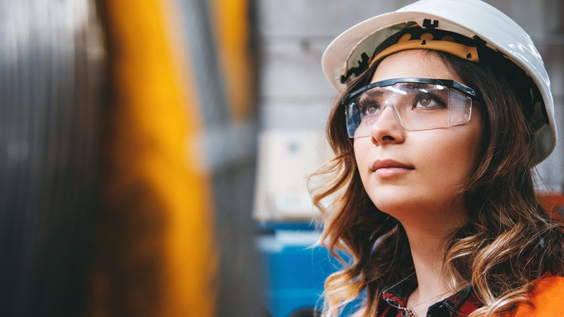 Young woman wearing protective eye wear and a hard hat, looking hopeful