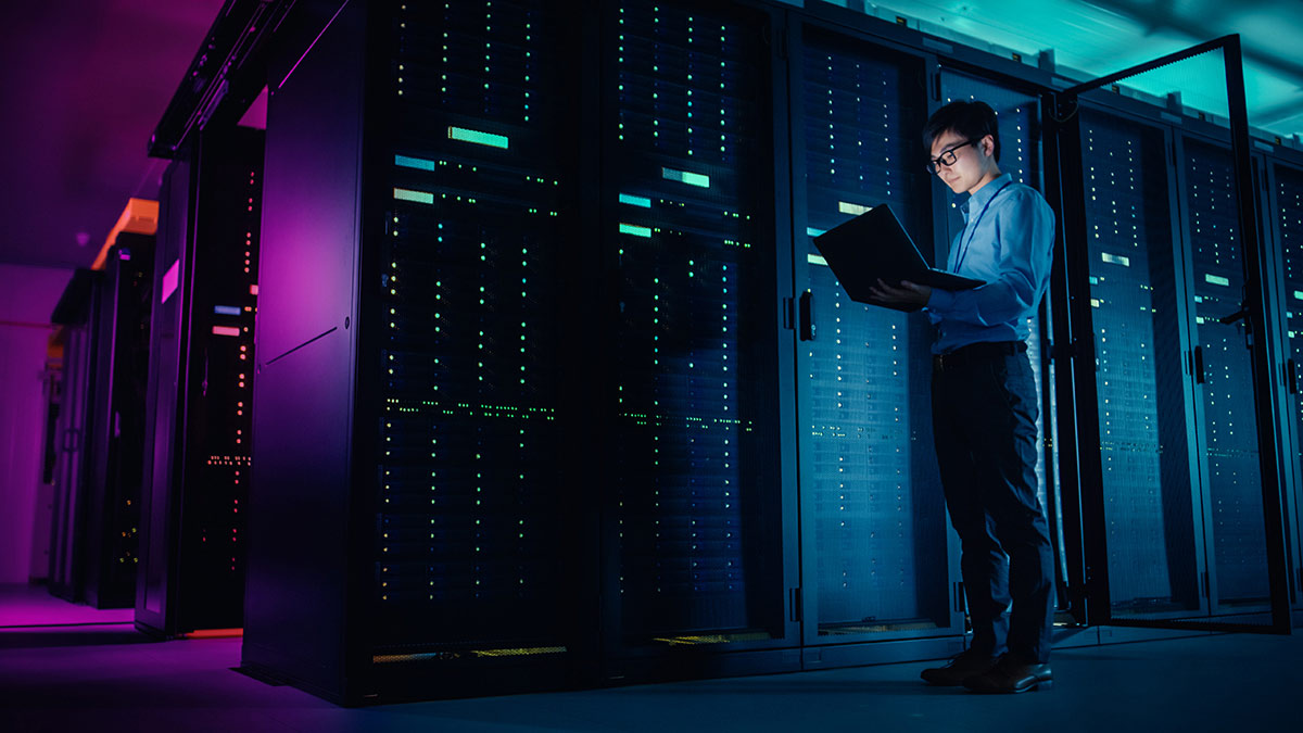 Young man illuminated by his laptop screen, standing in dimly lit server room