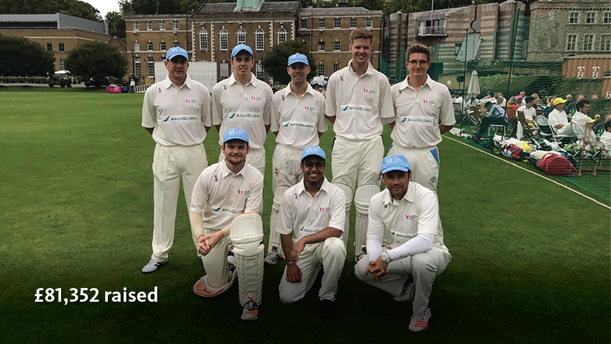Cricket team in branded Argo Group uniforms posing on lush green lawn