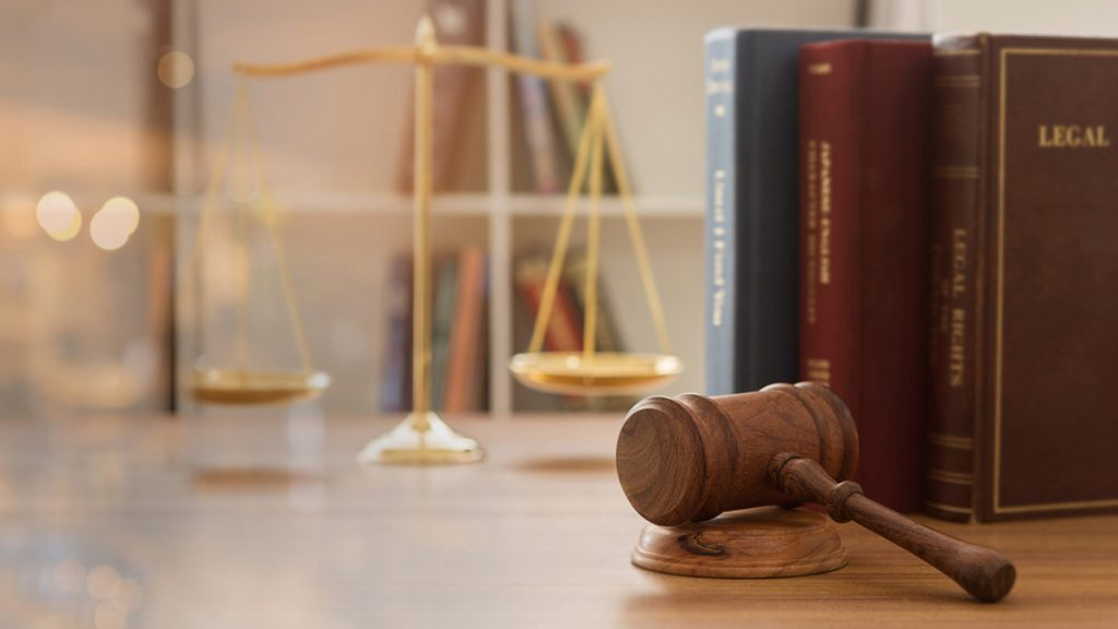 A gavel on a desk in front of the scales of justice and legal books